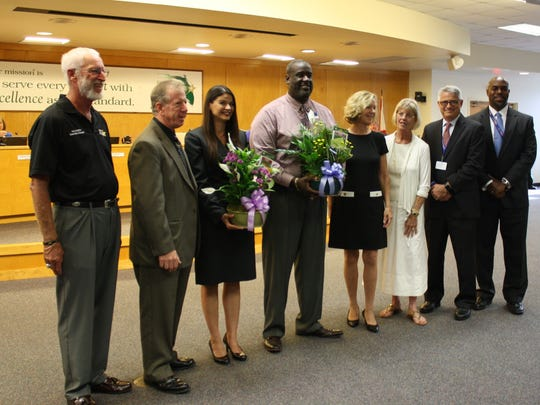 Meara Trine, left with flowers, and Rachad Wilson, right with flowers, were named Assistant Principal of the Year and Principal of the Year, respectively. Wilson is principal at Endeavor Elementary, and Trine served as assistant principal at Jackson Middle before being promoted to principal at Tropical Elementary. The duo was honored at Tuesday's school board meeting.
