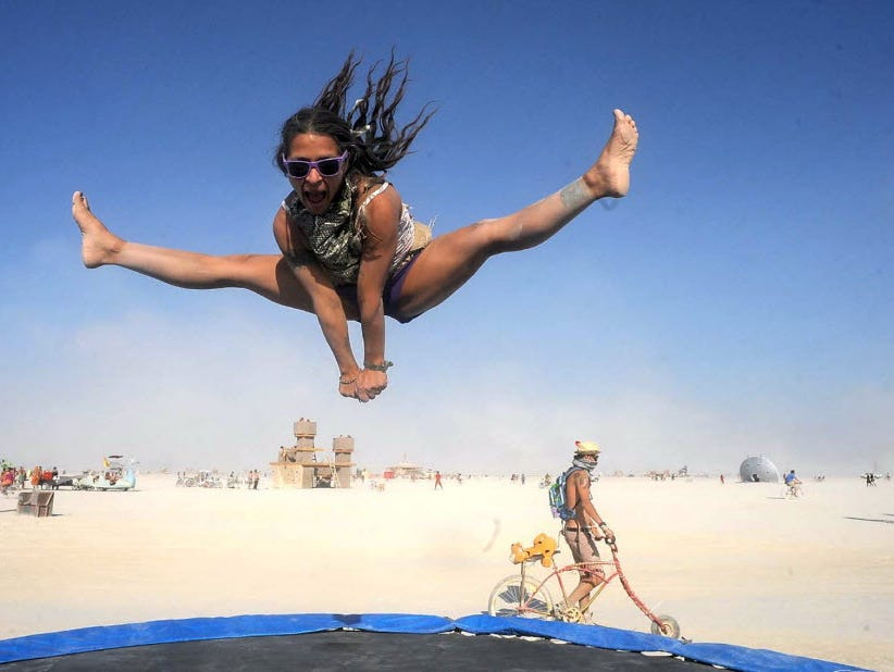 In this Aug. 29, 2013 photo, Selam Borges plays on a trampoline at Burning Man