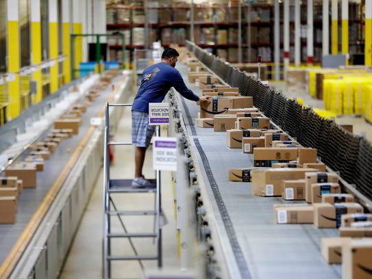 In this 2017 photo, an Amazon employee makes sure a