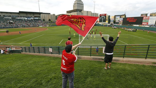 WNY Flash fan Sabrina Beach of Webster waves the team's flag as the Flash score against the Seattle Reign in the first half at Frontier Field. Beach has attended every game played by the Flash.
