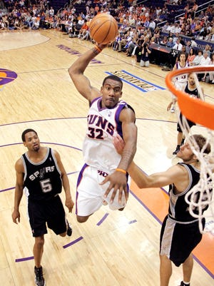 Phoenix Suns' Amare Stoudemire slam dunks the ball as San Antonio Spurs' Robert Horry, left, and Bruce Bowen, right, guard during game 1 of the Western Conference Finals, Sunday, May 22, 2005, in Phoenix. The Spurs won 121-114.