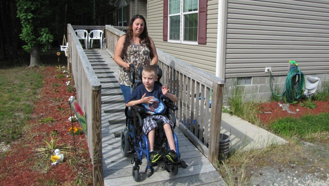 Danielle Twigg escorts her 9-year-old son, Layne, down a walkway outside. After losing out on a contest to win a wheelchair-accessible van, Danielle, has received an outpouring of support from the community.