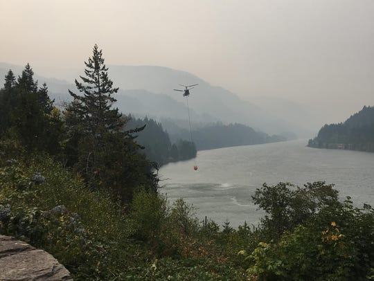 A helicopter takes water from the Columbia River near