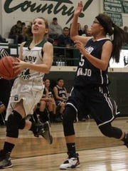 Sabina Judah, left, drives to the basket on Saturday night. Cloudcroft fell to Alamo Navajo 65-45 in the District 3-2A opener.