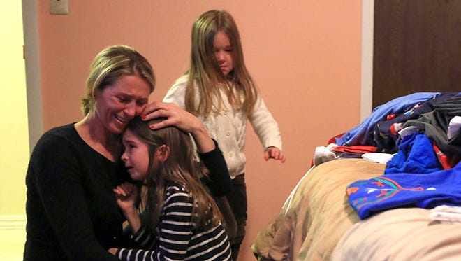 Cile Precetaj, 40, of Troy, Mich., packs Monday, Dec. 2, 2013, with children Migena Gojcaj, 6, and Martina, 4. She is scheduled to be deported to Albania Tuesday after she was denied political asylum.