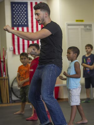 Dorian Montero shows students proper form at the Cobra Kai dojo in Cape Coral Thursday, August 6.
