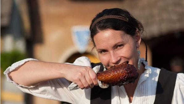 A wench digs in to a turkey leg, one of the most popular food offerings at the Minnesota Renaissance Festival.