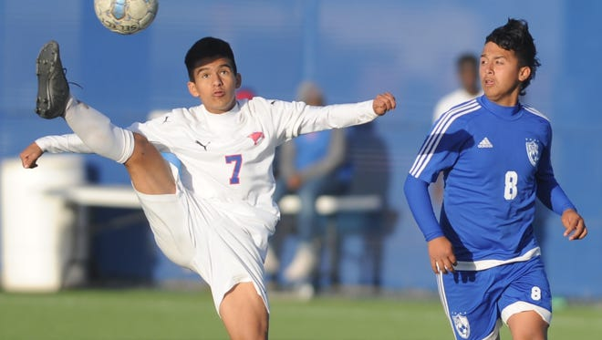 Cooper's Hector Tijerina (7) plays the ball while Amarillo Palo Duro's Andres Flores looks on. Palo Duro beat Cooper 3-2 in overtime in a Region I-5A bi-district playoff game Friday, March 24, 2017 in Wolfforth.