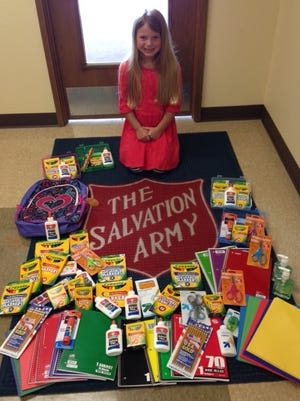 Lucy Fridley, 6, is surrounded by the school supplies she asked her birthday party guests to bring instead of presents for her. The supplies were part of the 2014 Back to School FDL school supply distribution to qualified area school students.