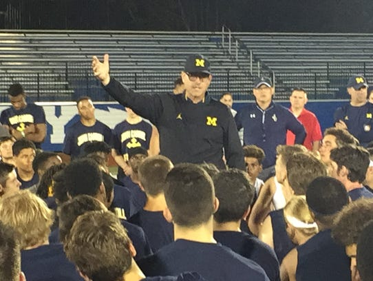 Michigan coach Jim Harbaugh addresses players at the
