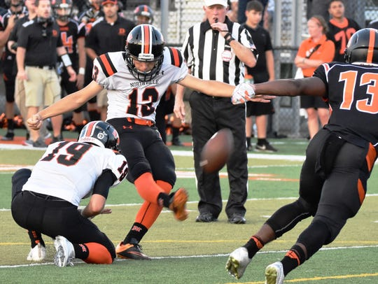 Northville's Jake Moody (middle) boots one of his two
