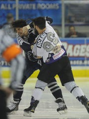 Ice Flyers' Joe Bueltel (left) and Knoxville Icebears' Dennis Sicard, fight at center ice Sunday at the Pensacola Bay Center.