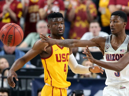 Arizona's Dylan Smith, right, passes the ball while covered by Southern California's Chimezie Metu during the first half of an NCAA college basketball game in the Pac-12 men's tournament final Saturday, March 10, 2018, in Las Vegas. (AP Photo/Isaac Brekken)