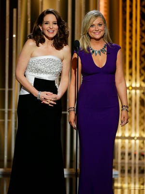 Co-hosts Tina Fey (left) and Amy Poehler speak during the 72nd Annual Golden Globe Awards on Sunday, Jan. 11, 2015, at the Beverly Hilton Hotel in Beverly Hills.