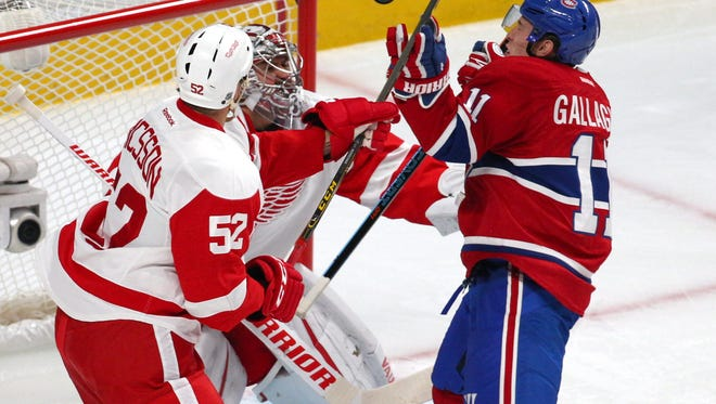 Red Wings goalie Petr Mrazek (34) and defenseman Jonathan Ericsson (52) eye the puck and Canadiens right wing Brendan Gallagher (11) during the first period Saturday in Montreal.