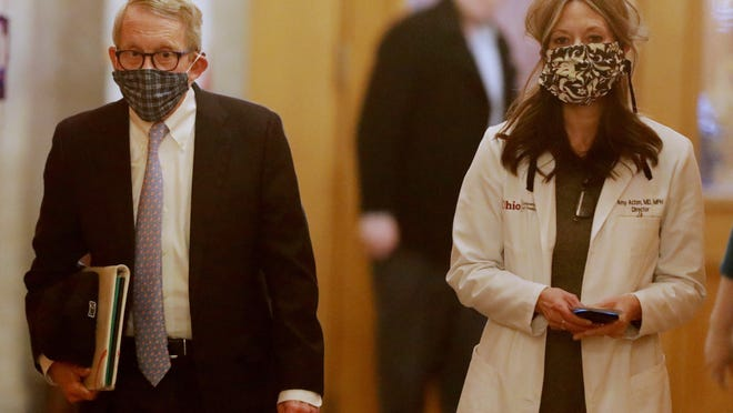Ohio Gov. Mike DeWine and Ohio Health Director Dr. Amy Acton walk into their daily coronavirus news conference in April when they were still being held in the Statehouse.