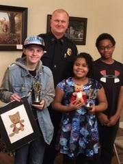 Gallatin Police Chief Don Bandy poses with Creative Critter winners Cheyenne Calvert of Beech High School and Aubrey and Cameron Taylor of Children Are People, Inc.