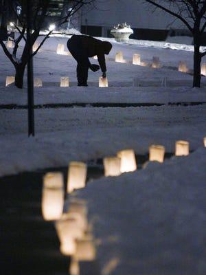 A resident lights a luminary in Irvington.