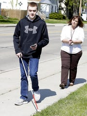 Baylee Alger, 17, walks along Shawano Avenue in front of West High School while using a new navigation phone app for the visually impaired with assistance from Cindy Lambert, Green Bay Area Public Schools teacher for the visually impaired.