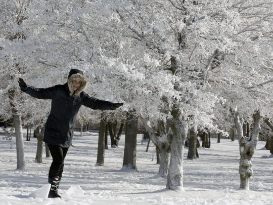 A woman keeps her balance while walking under trees