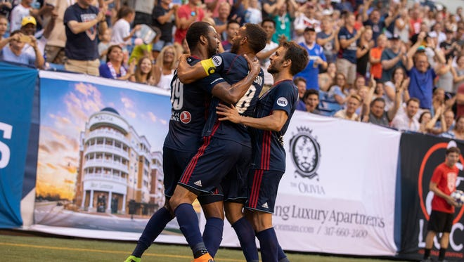Indy Eleven's Carlyle Mitchell (left) celebrates his winner with teammates Saturday night at Lucas Oil Stadium.