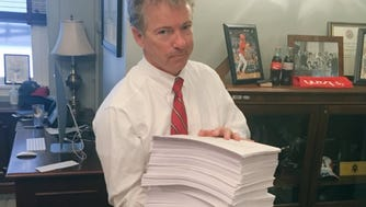 Sen. Rand Paul gets ready to read the omnibus spending bill and tweet about it March 22, 2018.