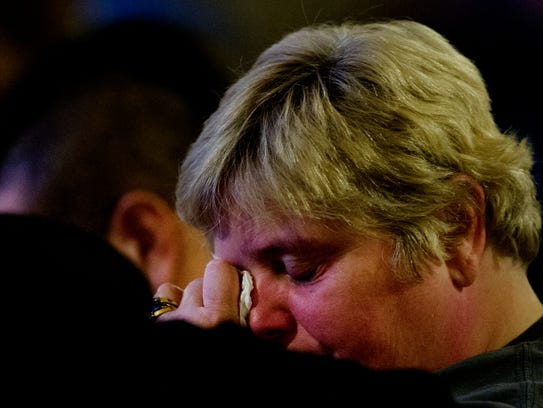 An attendee weeps during a memorial service held at