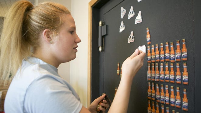 Tour guide Corrina Suess of Oshkosh restocks bottle magnets in the gift shop at Point Brewery, Thursday, June 25, 2015.