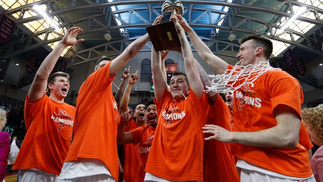 Princeton holds up the Ivy League Basketball Tournament Trophy Sunday. The Tigers are back in the NCAA Tournament.