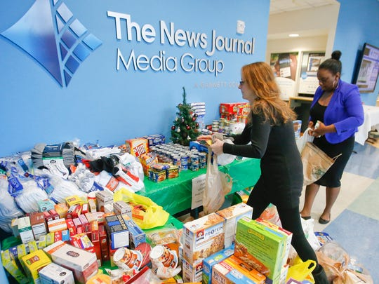 Debbie Shelton (left) and Chanell Lewis organize collections at The News Journal's drop off site in the Stockings for Soldiers campaign Saturday. Donations can be made through Tuesday.