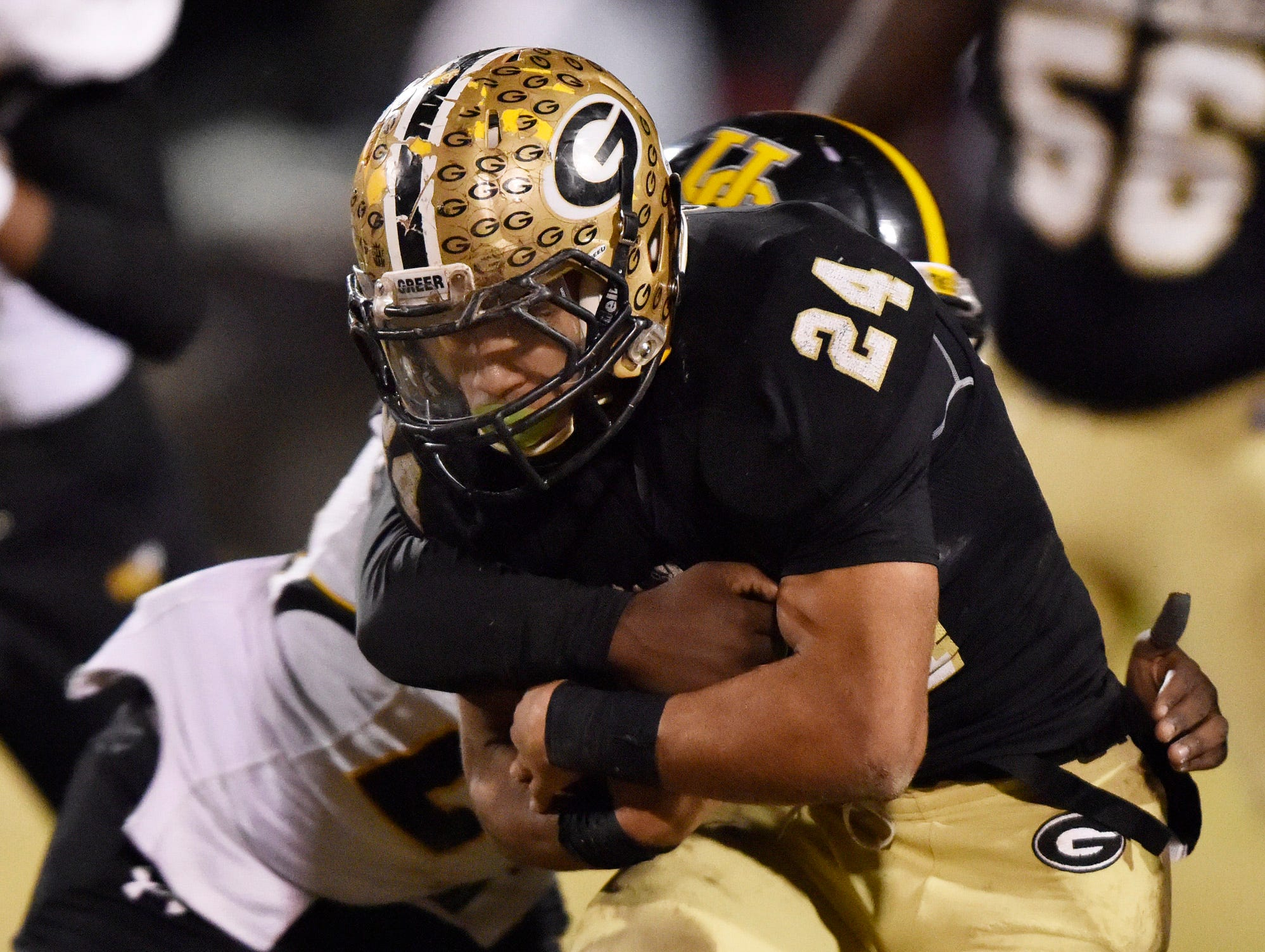 Greer's Adrian McGee (24) sheds a Union County tackler.