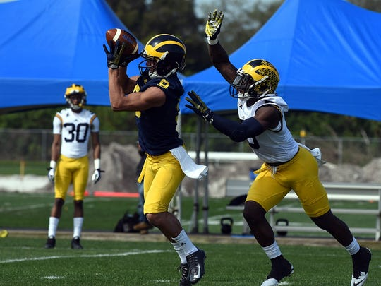 Michigan receiver Grant Perry catches a pass while safety Jabrill Peppers defends during Michigan's practice Monday.
