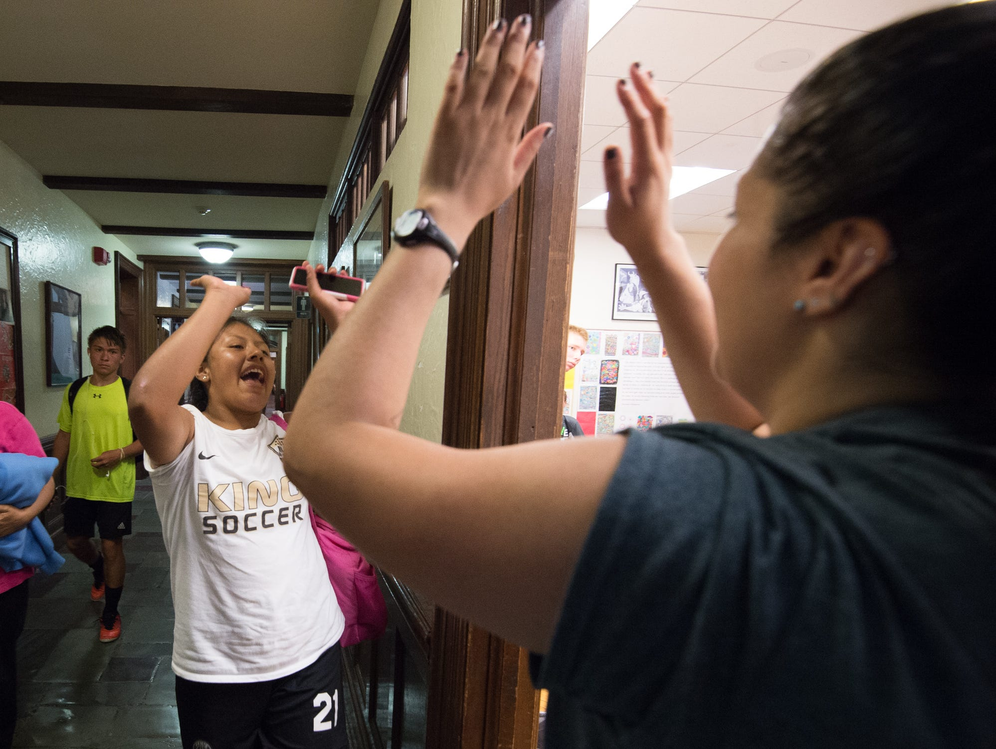 Mechelle Perez, left of Queens, N.Y., receives a high five from Strive Sports Challenge director, Sabrina Zurkuhlen, before a classroom instruction session at the Strive Sports Challenge at St. Andrew's School in Middletown, Del,.