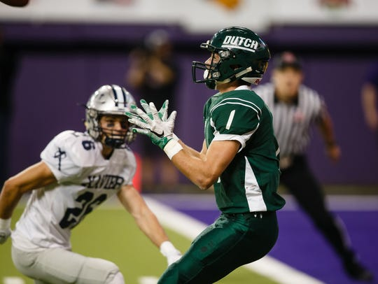 Pella's Avery Van Zee catches a pass and runs it in