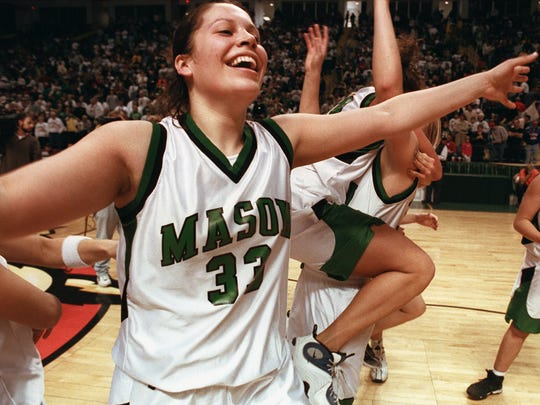 Text: 1999.0312.12.1 -- BASKETBALL SPORTS -- Mason's Michelle Munoz and her teammates race onto the court Saturday to celebrate after defeating Beavercreek 61-55 during the Division 1 Girls Regional Tournament at Wright State University.