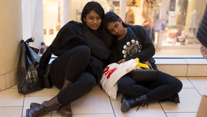 Tired shoppers take a break. Visitors to Freehold Raceway Mall in the early morning hours shop for bargains and more. The Mall was open as well yesterday so there wasn't the rush as in past years but interest in shopping was still high.