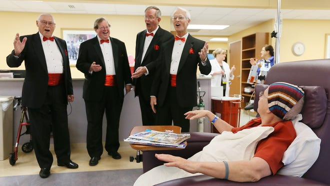 Walter Smith, left, John Braden, Robert Brutsman and Dave Barton serenade patients to include Nellie Vega at the Lee Memorial Regional Cancer Center on Friday in Fort Myers. The quartet spent much of the day delivering happy Valentine's Day melodies to sweethearts throughout Southwest Florida.