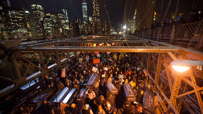 People march over the Brooklyn Bridge to protest the decision of a grand jury not to indict a police officer involved in the death of Eric Garner in New York on Dec. 4.