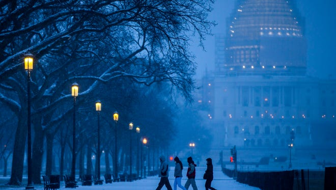 Pedestrians walk across the National Mall in Washington as the U.S. Capitol looms in the background on Feb. 16, 2015.