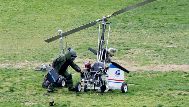 A member of a bomb squad works beside a gyrocopter after it landed on the West Front of the U.S. Capitol on April 15, 2015.