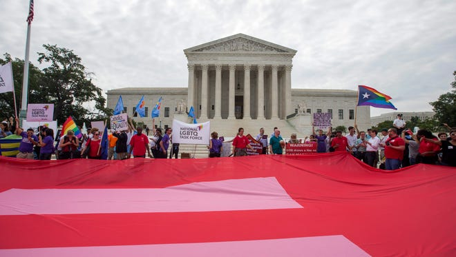 Supporters of gay marriage unfurl an equality flag outside the Supreme Court on June 26, 2015.