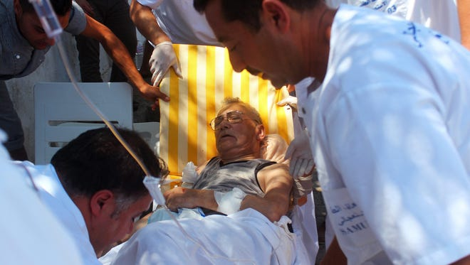 Medics help an injured man in Sousse, Tunisia, on June 26, 2015 after gunmen opened fire on a resort beach.