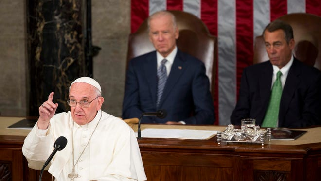 Pope Francis delivers a much-anticipated speech between Vice President Joe Biden, left, and Speaker of the House John Boehner, right, on the floor of the House of Representatives to Congress in the  in Washington DC, on September 24, 2015.