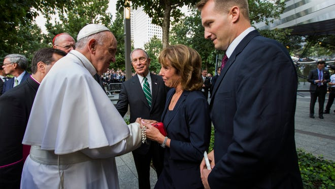 epa04949381 Pope Francis greets family members of victims of the September 11, 2001 attacks in front of former New York City Mayor Michael Bloomberg while visiting the 9/11 Memorial plaza in New York, USA, 25 September 2015. Pope Francis is on a five-day trip to the USA, which includes stops in Washington DC, New York and Philadelphia, after a three-day stay in Cuba.  EPA/JIN LEE / POOL