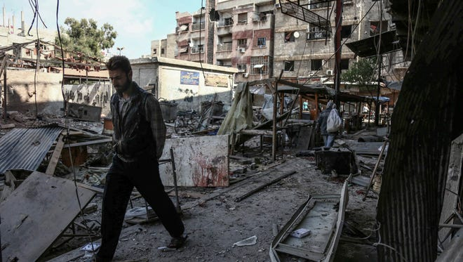 A Syrian walks through a destroyed market place following what local activists say was an airstrike by forces loyal to the al-Assad regime in the rebel-held area of Douma, outskirts of Damascus, Syria, Oct. 30, 2015.