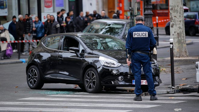 A French police officer stands near car linked to Friday's attacks in Paris on Tuesday, Nov. 17, 2015. as part of a massive police investigation operations in Paris, France, 17 November 2015. More than 130 people have been killed in a series of attacks in Paris on 13 November, according to French officials. Eight assailants were killed, seven when they detonated their explosive belts, and one when he was shot by officers, police said. French President Francois Hollande says that the attacks in Paris were an 'act of war' carried out by the Islamic State extremist group.  EPA/YOAN VALAT ORG XMIT: YOV03