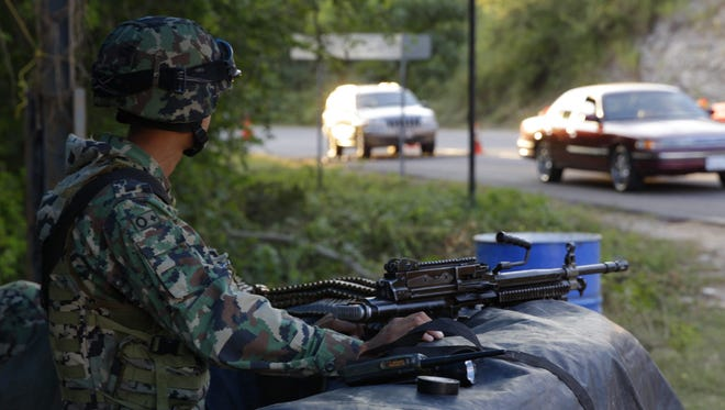 """Mexican Navy soldiers guard at a check point on a road during a search operation for drug lord Joaquin """"El Chapo"""" Guzman, outside Cosala, Sinaloa, Mexico, on Oct. 22, 2015."""