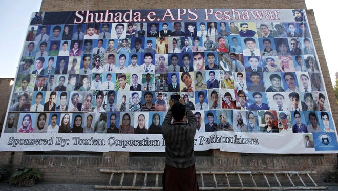 A boy takes a picture of the portraits of the victims of a Pakistani Army school attack on Dec. 15, 2015, the eve of the first anniversary of the terrorist massacre, in Peshawar, Pakistan.