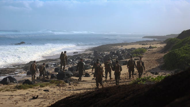 A handout picture made available by the Marine Corps shows Marines searching for debris of two CH-53E Super Stallion helicopters along the coast of Haleiwa, Hawaii, on Jan. 16, 2016.