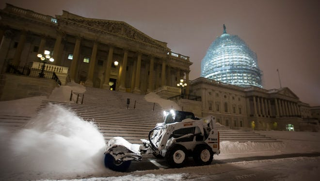 Workers struggle to clear snow from the East Front of the US Capitol early in the morning during a major blizzard that threatened to cause widespread power outages.